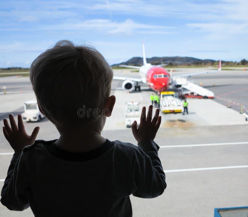 Мальчик смотря через окно на авиапорте стоковое фото rf