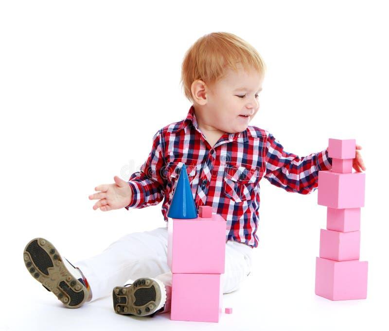 Мальчик собирает розовую пирамиду стоковая фотография