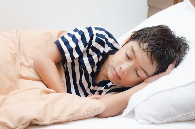 Мальчик спать на кровати стоковые фотографии rf