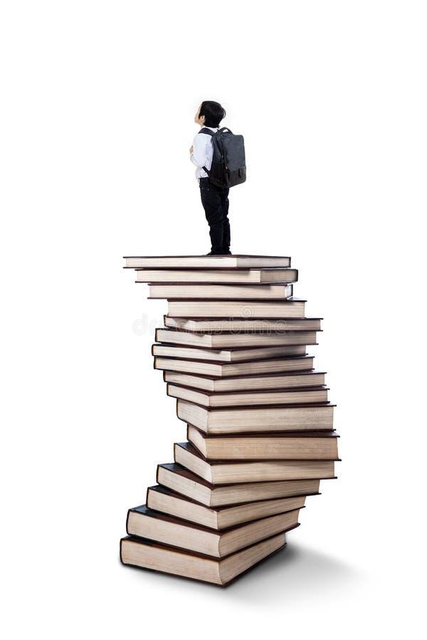 Мальчик стоя на стоге книг стоковые фотографии rf