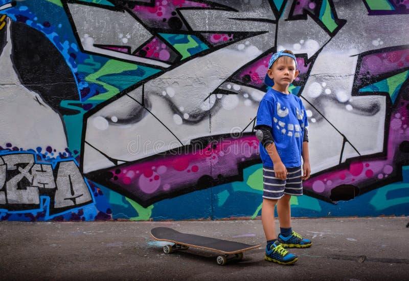 Мальчик стоя перед живыми граффити стоковые изображения