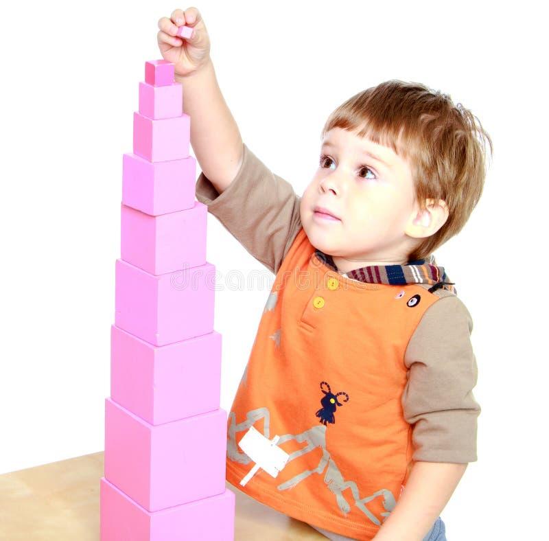 Мальчик строит розовую башню стоковые изображения