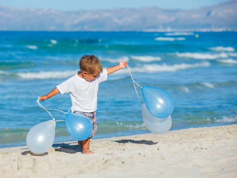 Мальчик с баллонами на пляже стоковое фото rf