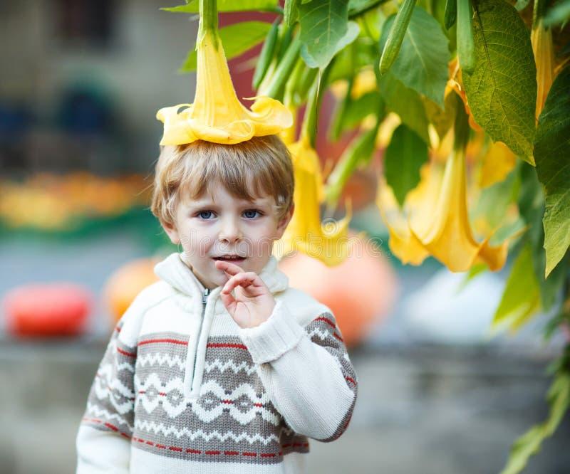 Мальчик с большим желтым цветком стоковая фотография