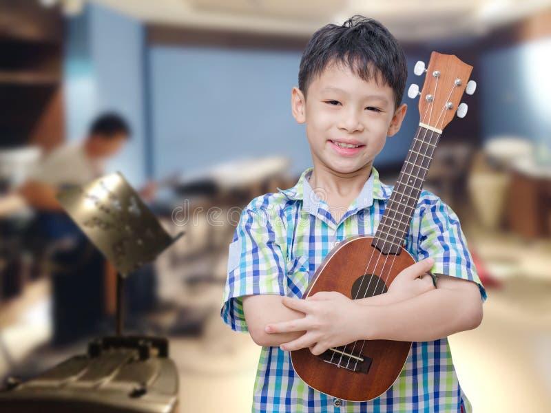 Мальчик с гавайской гитарой на музыкальной школе стоковые изображения