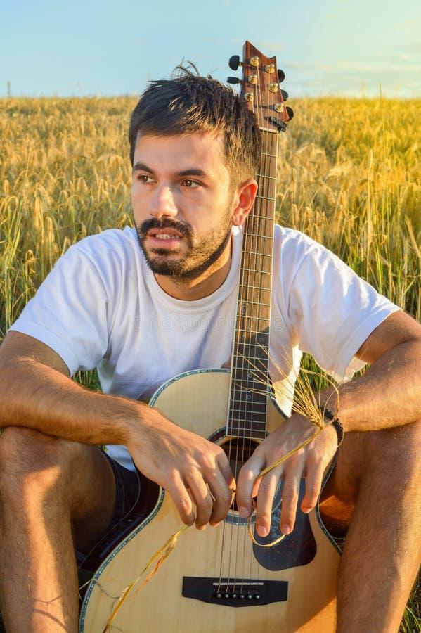 Мальчик с гитарой в поле стоковое изображение
