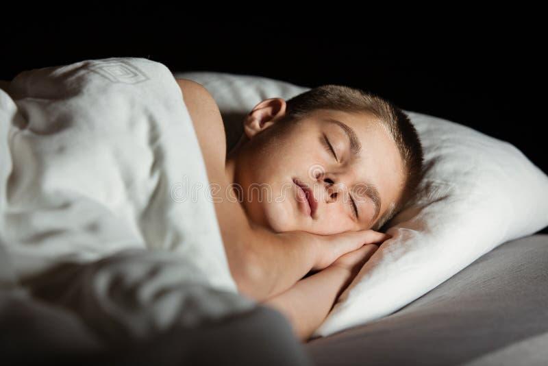 Мальчик с глазами закрыл уснувшее в кровати стоковая фотография