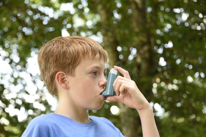 Мальчик с ингалятором астмы стоковые изображения