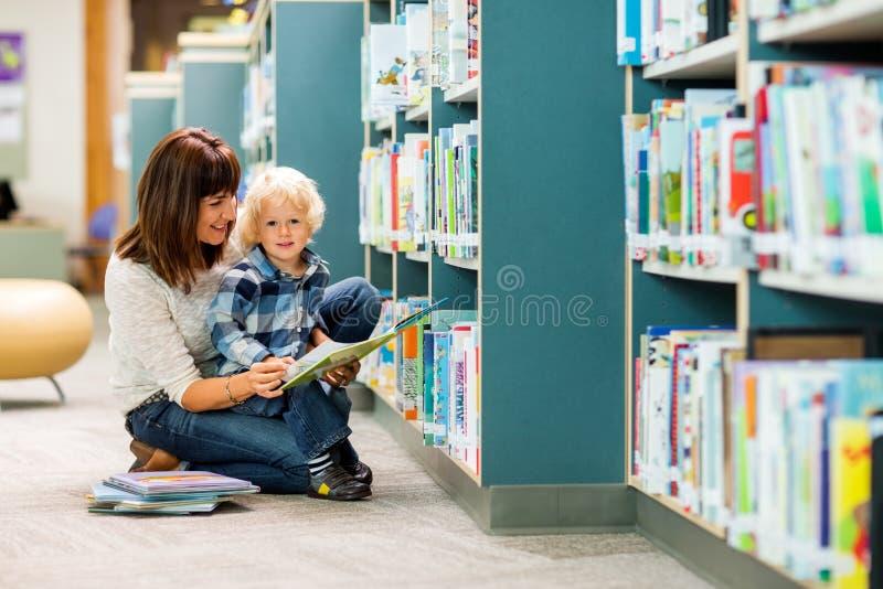 Мальчик с книгой чтения учителя в библиотеке стоковые фотографии rf