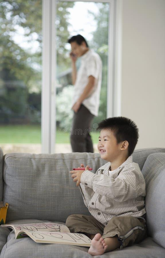 Мальчик с книжка-раскраской пока отец на звонке дома стоковая фотография