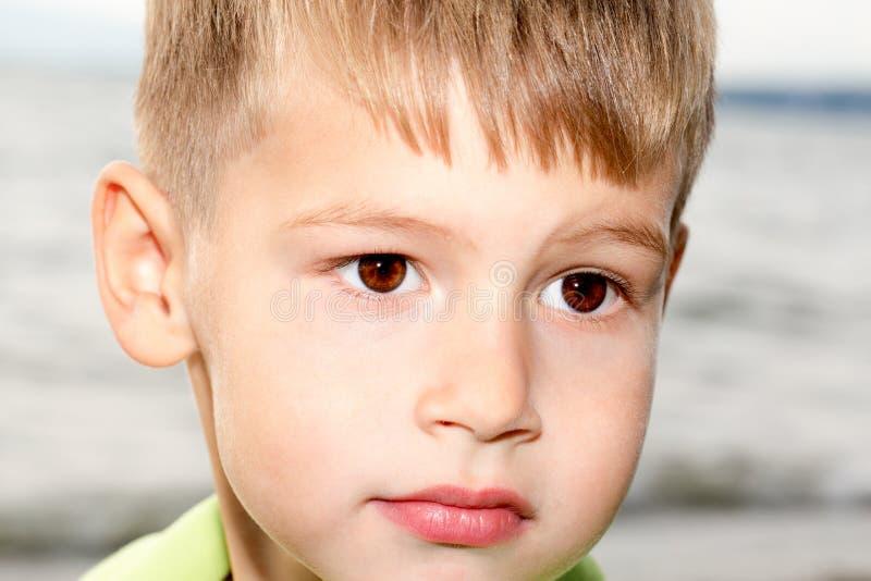 Мальчик с красивыми глазами на береге моря стоковые изображения