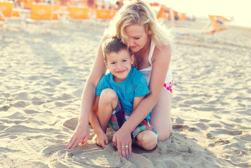 Мальчик с мамой на пляже стоковые фотографии rf