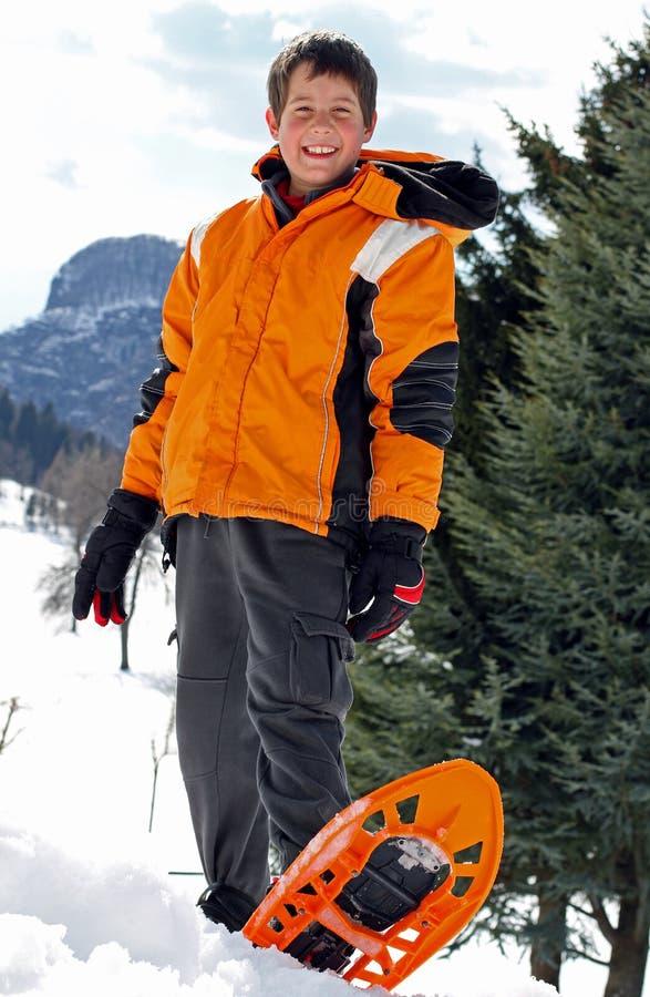 Мальчик с одеждой и snowshoes зимы стоковые фото