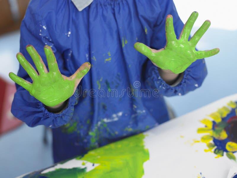 Мальчик с покрашенными руками в художественном классе стоковое фото