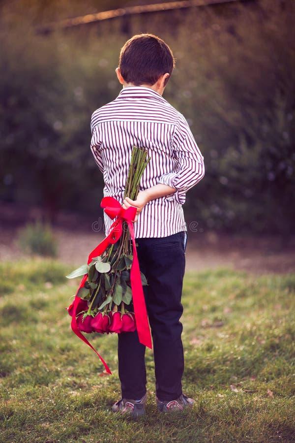 Мальчик с пуком красных роз стоковые изображения rf