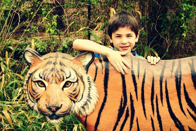 Мальчик с статуей тигра стоковая фотография