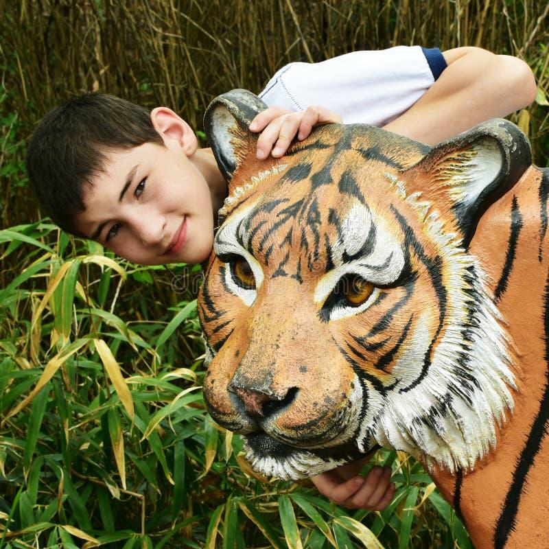 Мальчик с статуей тигра стоковые фото