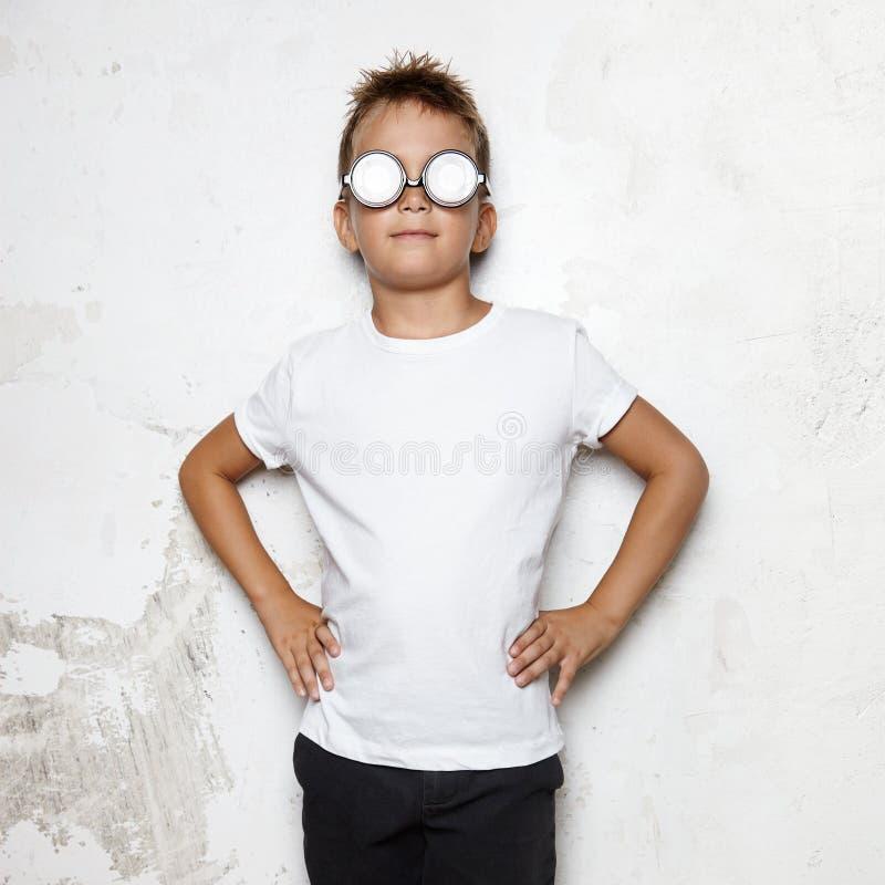 Мальчик с стеклами стоит на предпосылке стены и стоковые фото