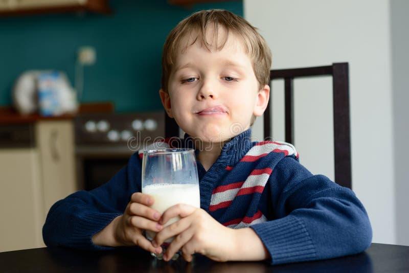 Мальчик с стеклом очень вкусного молока стоковая фотография rf