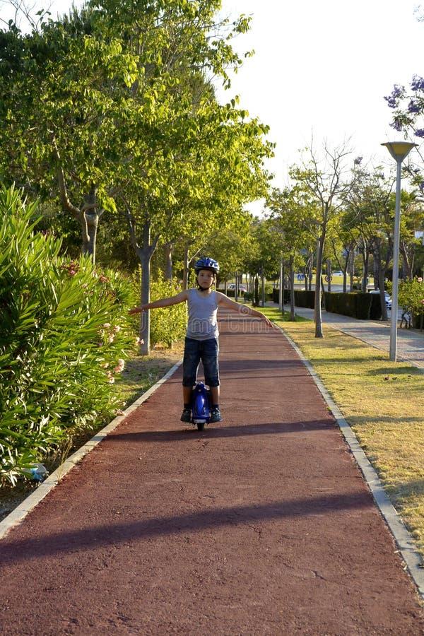 Мальчик с шлемом едет MonoWheel на прогулке стоковое изображение rf