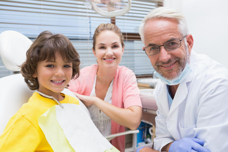 Мальчик усмехаясь на камере с матерью и дантистом около его стоковое изображение rf