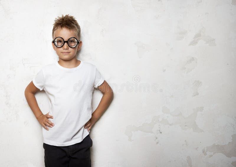 Мальчик усмехаясь на конкретной предпосылке и стоковые изображения