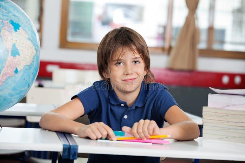 Мальчик усмехаясь пока сидящ с глобусом и стоковая фотография rf