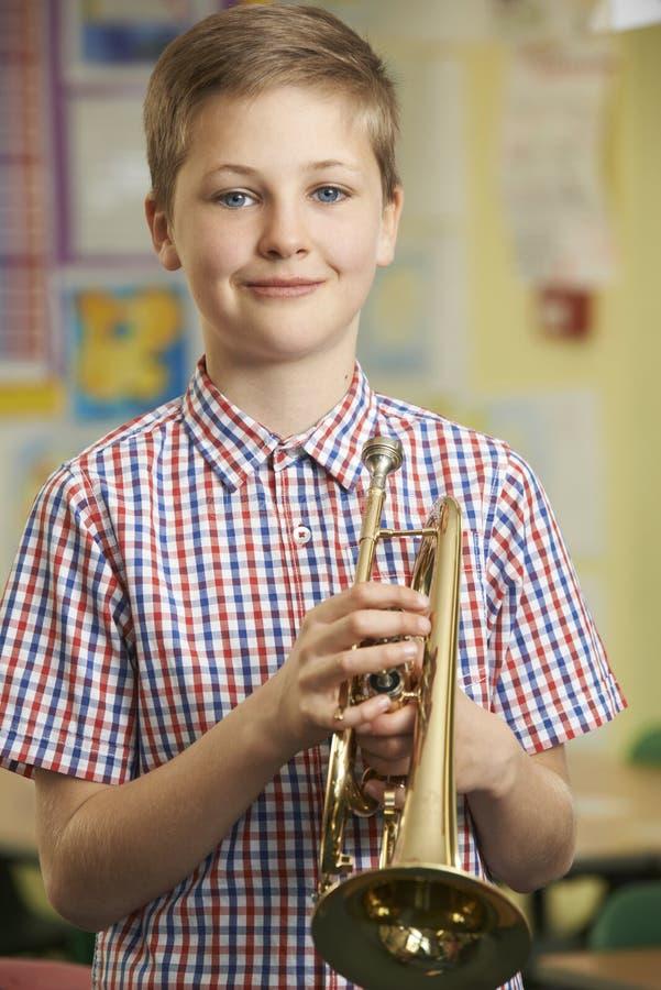 Мальчик уча сыграть трубу в уроке музыки школы стоковая фотография