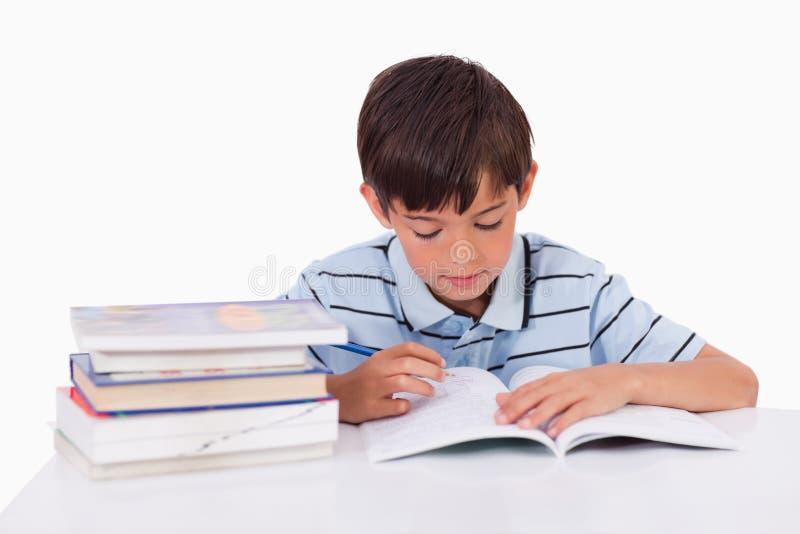 Мальчик учя его уроки стоковые изображения