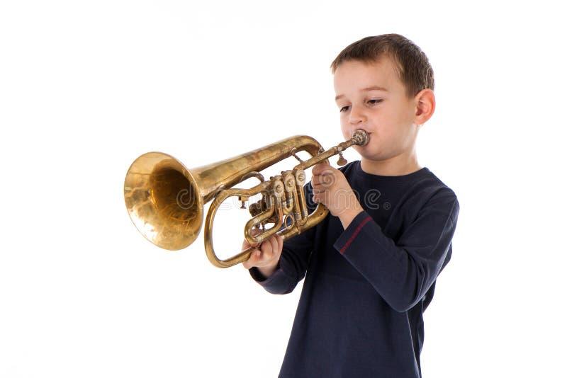 Мальчик дуя в трубу стоковое изображение