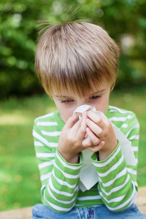 Мальчик дуя его нос в саде стоковые фото