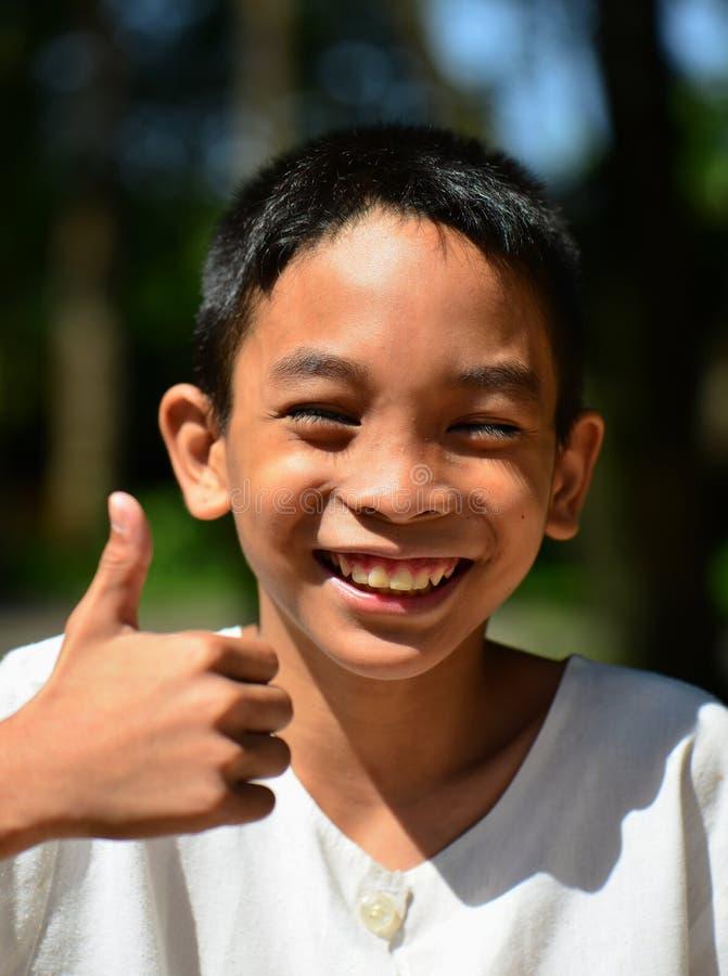 Мальчик улыбки азиатский с thump вверх стоковое изображение
