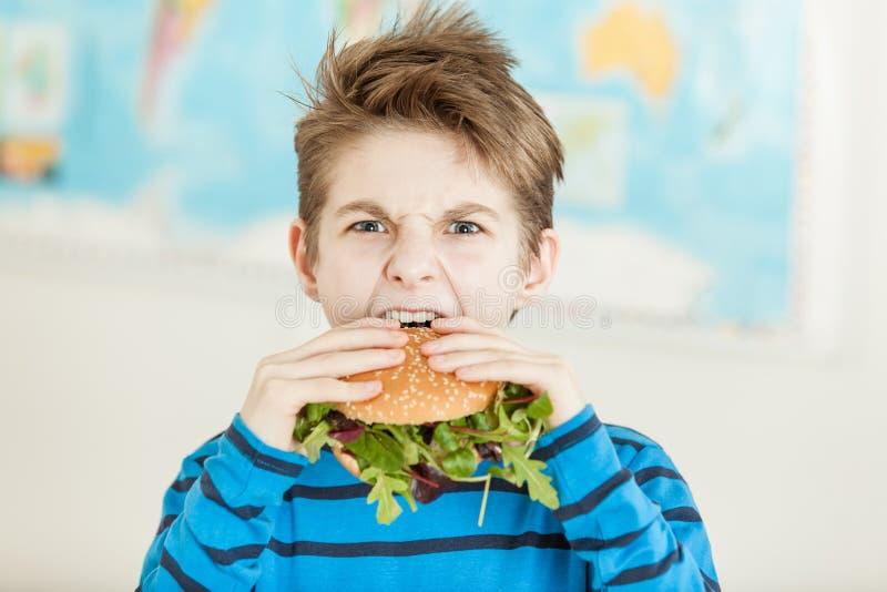Мальчик хмурясь как он сдерживает в бургер veggie стоковые изображения rf