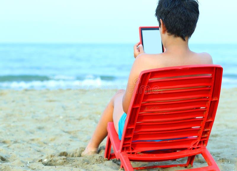 Мальчик читает ebook на красных стульях стоковое фото rf