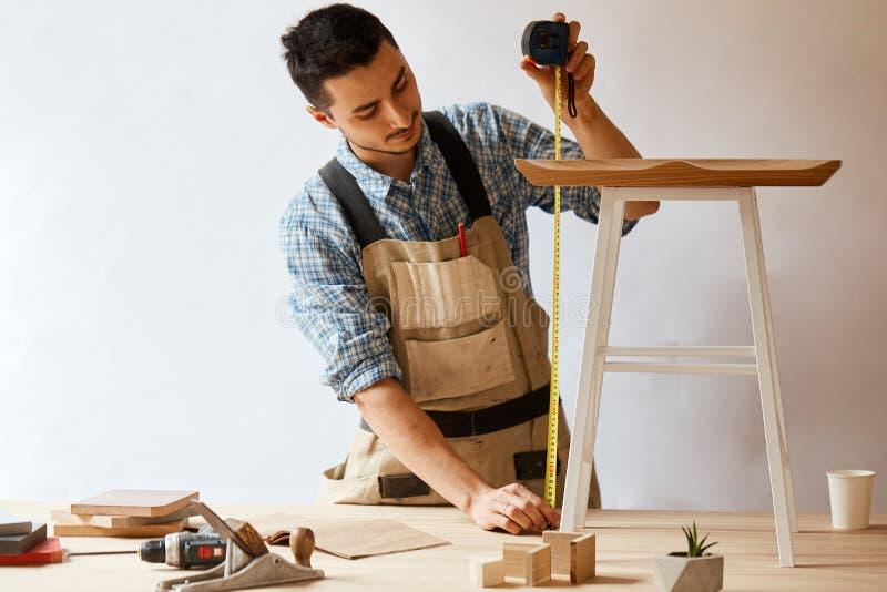 Мебель молодого человека измеряя домашняя с лентой измерения Отремонтируйте принципиальную схему стоковые изображения