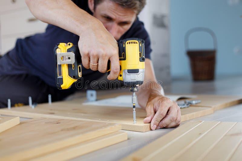 Мебель человека собирая дома используя бесшнуровую отвертку стоковая фотография