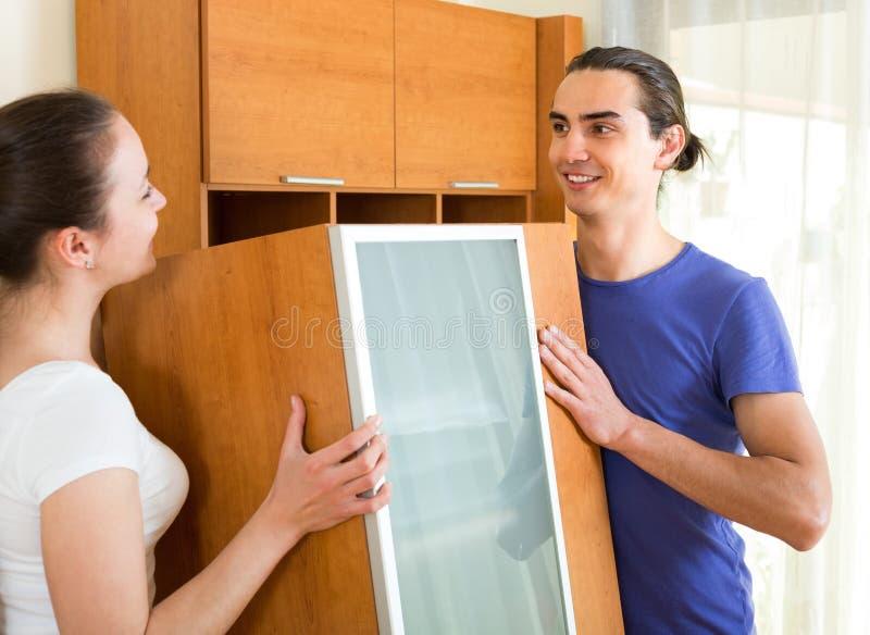 Мебель пар moving в комнате стоковое изображение