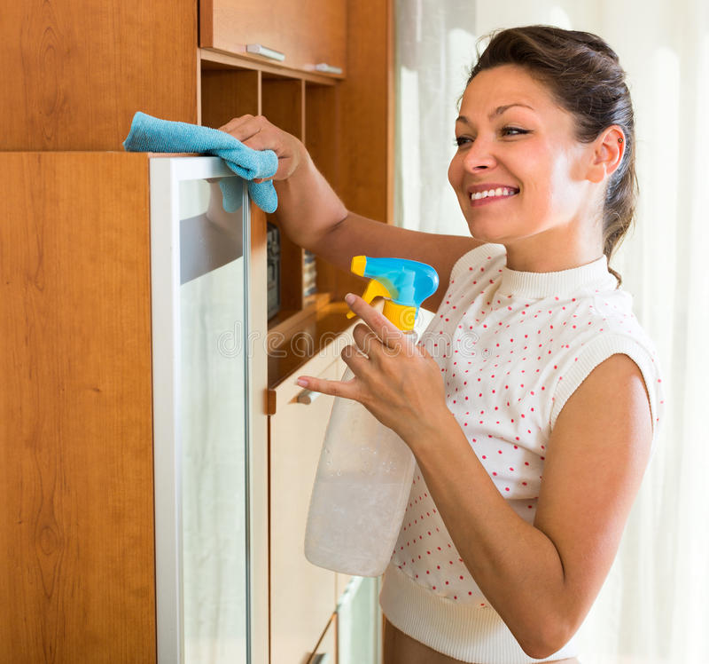 Мебель чистки домохозяйки с спрейером стоковое фото rf