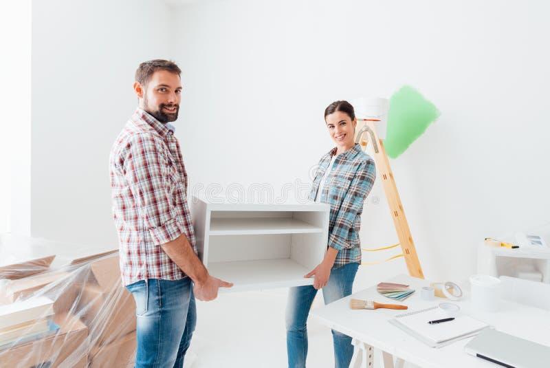 Меблировкы пар moving в их новом доме стоковое фото