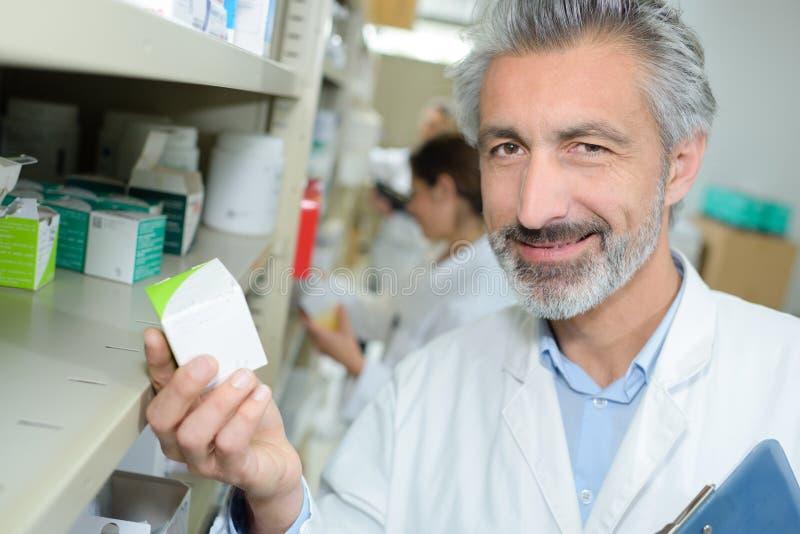 Медицина дружелюбного мужского аптекаря распределяя держа таблетки коробки стоковое фото rf
