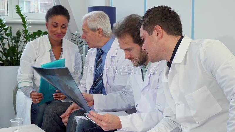 Медицинская бригада обсуждает изображение рентгеновского снимка стоковое изображение rf