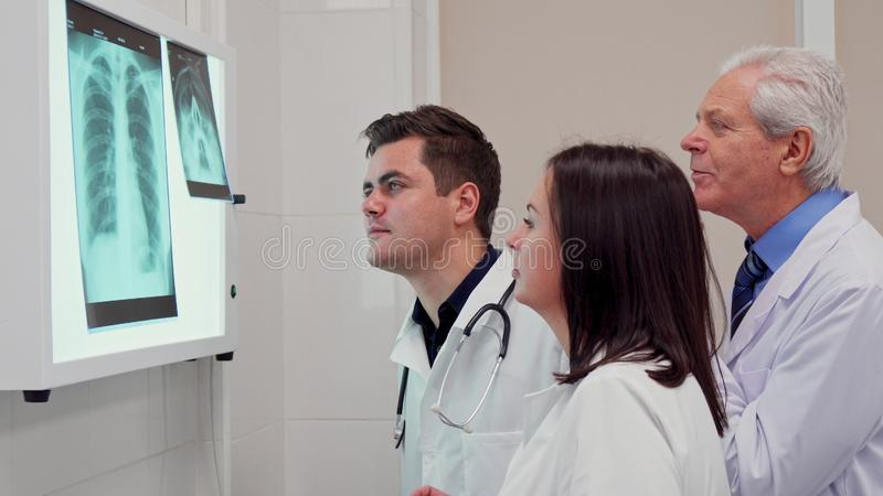 Медицинская бригада analizes рентгеновский снимок на коробке взгляда рентгеновского снимка стоковое фото