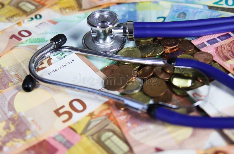 Медицинская стоить концепция - стетоскоп на бумажных деньгах денег бумаги евро и европейских монетках стоковая фотография