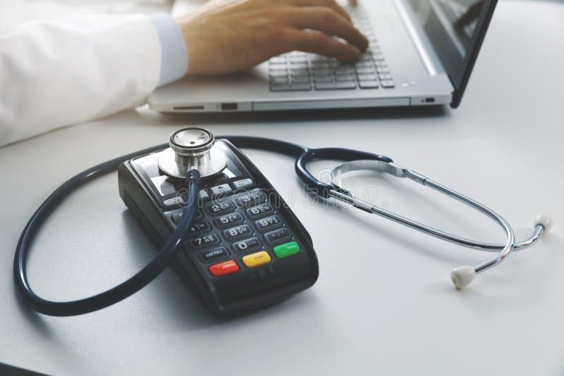 медицинские цены и концепция расходов здравоохранения - терминал оплаты со стетоскопом на таблице стоковые фото