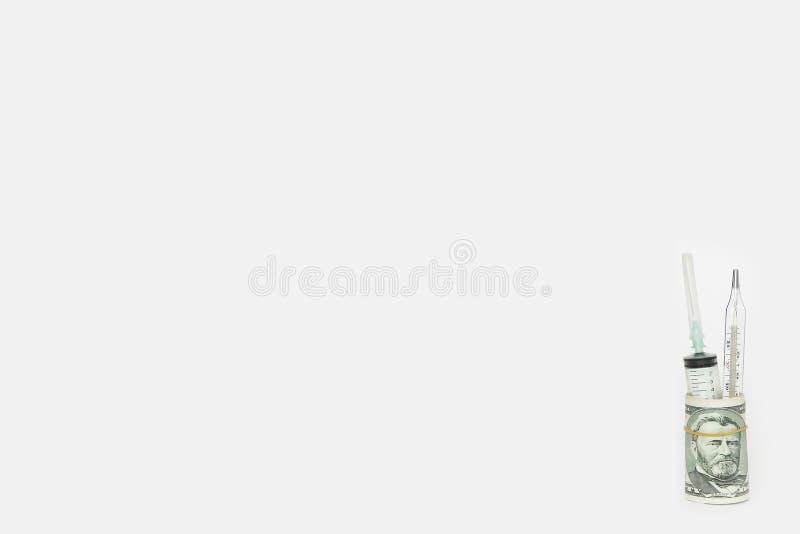 Медицинские шприц и термометр в крене долларов на белой предпосылке стоковое фото