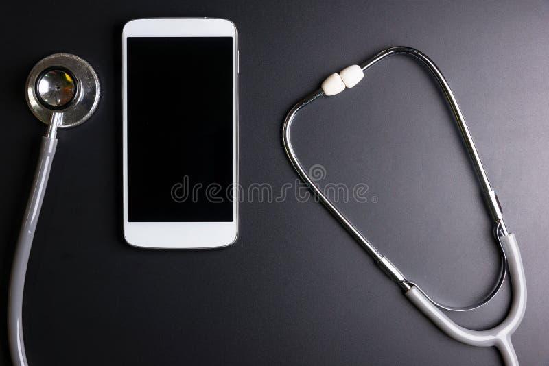 Медицинский инструмент стетоскопа над поверхностью мобильного умного phon стоковое фото rf