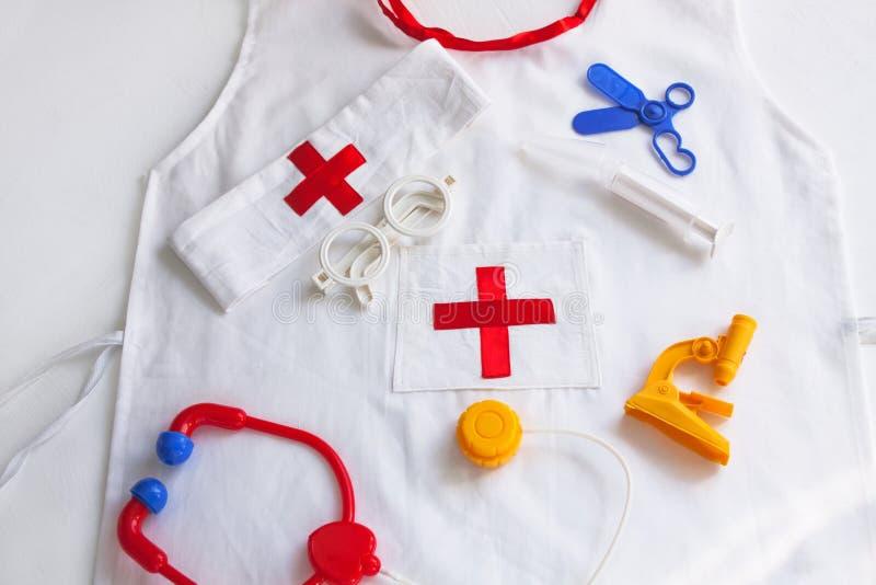 Медицинский комплект и лабораторное пальто для детей на белом фоне стоковое фото rf
