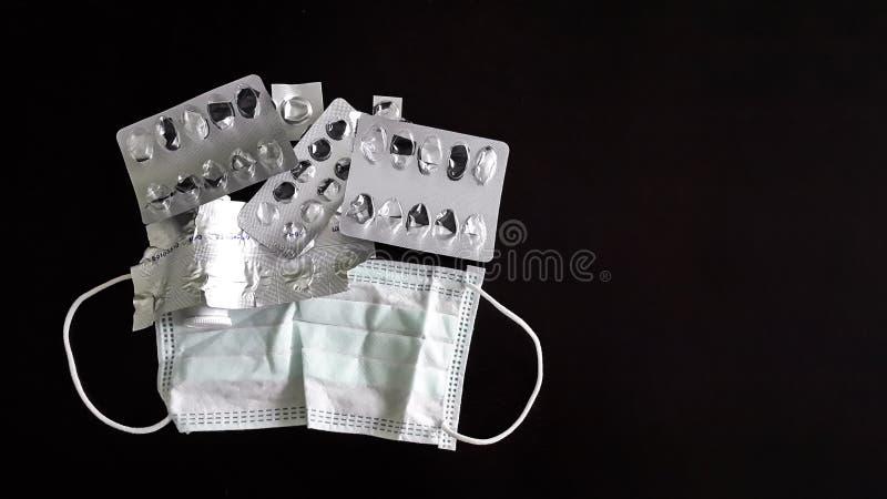 Медицинский лицевой щиток гермошлема и используемые пакеты пилюлек изолированных на черной предпосылке Хирургическая маска Ух-пет стоковое фото
