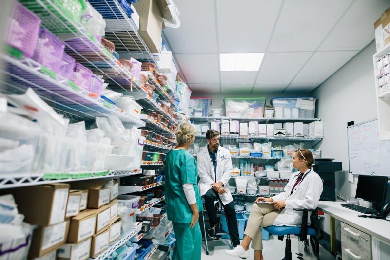 Медицинский персонал обсуждая в фармации больницы стоковое фото