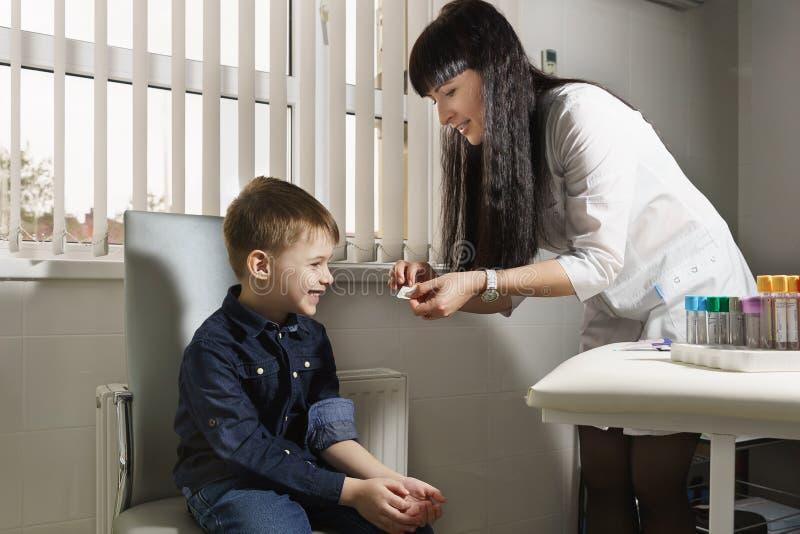 Медицинский работник раскрывает бактерицидную диапазон-помощь и с улыбкой клеит ее на ране к мальчику стоковая фотография rf